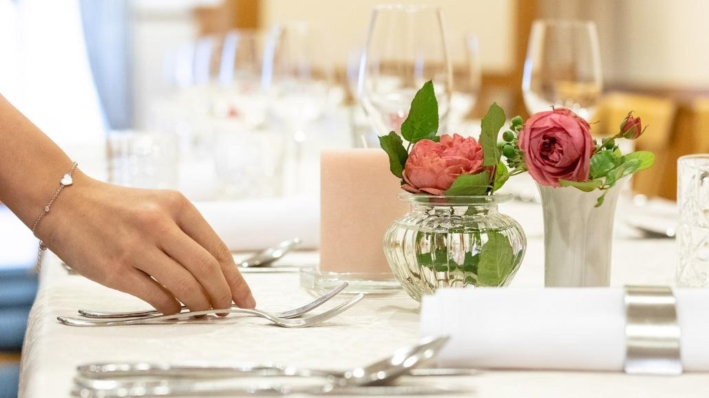 Frauenhand deckt Tisch